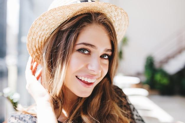 Retrato de primer plano de niña emocionada con piel pálida y grandes ojos grises feliz posando