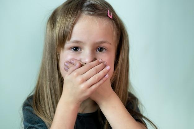 Retrato de primer plano de niña niño con cabello largo cubriendo su boca con las manos.
