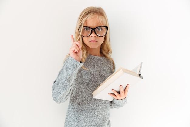 Retrato de primer plano de niña seria en gafas para adultos sosteniendo el libro, apuntando con el dedo hacia arriba