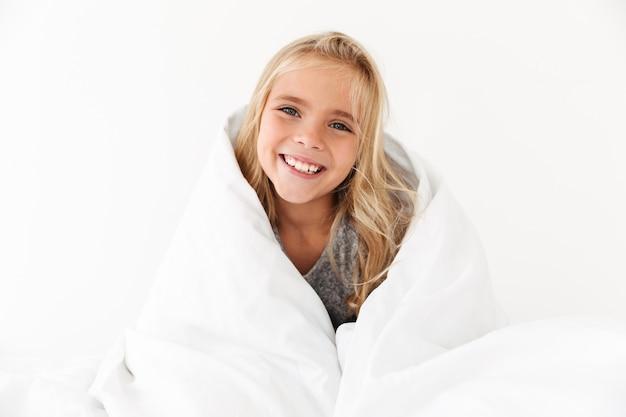 Retrato de primer plano de niño sonriente que cubre con una manta blanca,