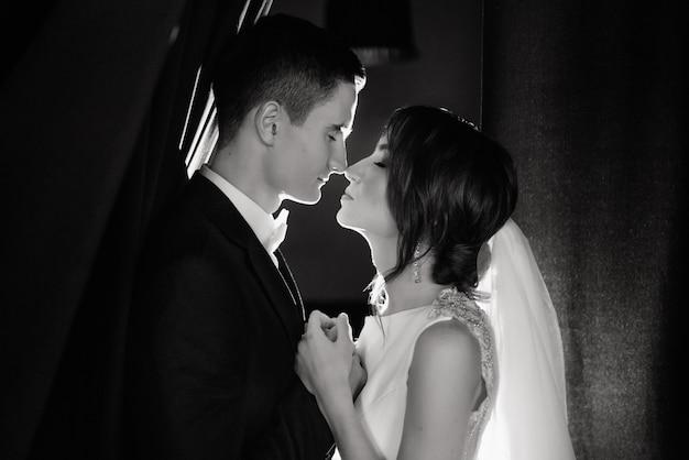 Retrato de primer plano de novia y el novio en el día de la boda. los recién casados con los ojos cerrados se tocan las narices.
