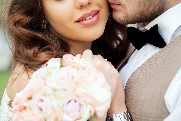 Retrato de primer plano de una novia y el novio de pie en la calle de la ciudad y un abrazo encantador