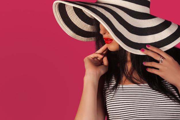 Retrato de primer plano o atractiva mujer con sombrero protector solar despojado. mujer hermosa irreconocible en pared rosa