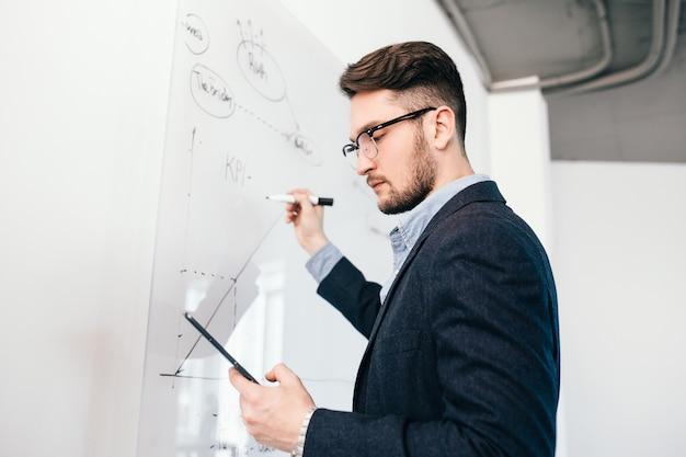 Retrato de primer plano de oung hombre de pelo oscuro con gafas con portátil escribiendo un plan de negocios en la pizarra. viste camisa azul y chaqueta oscura. vista inferior.