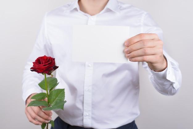 Retrato de primer plano recortada de guapo feliz encantador alegre alegre chico sosteniendo una pequeña tarjeta postal en las manos mostrando aislado espacio de copia de pared gris