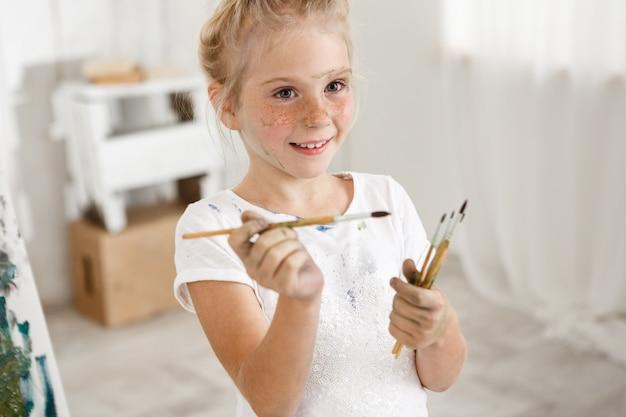 Retrato de primer plano de rubia linda niña europea con pintura en su cara pecosa y bollo de pelo sonriendo con todos sus dientes sosteniendo un montón de cepillos en sus manos. chica alegre estropeó su blanco