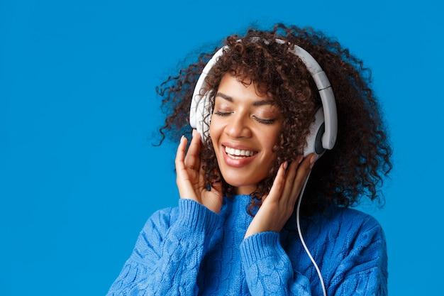 Retrato de primer plano tierno y despreocupado feliz, sonriente, mujer afroamericana sensual con auriculares grandes, ojos cerrados y sonrisa romántica recordar buenos recuerdos de escuchar canción, azul