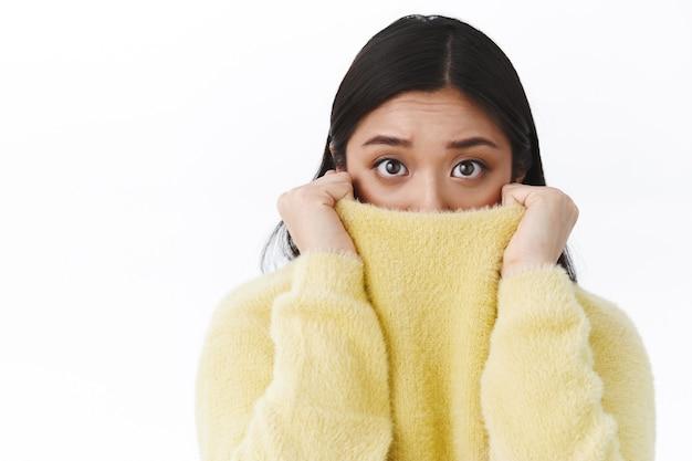 Retrato de primer plano tímida e insegura linda chica asiática tirando del cuello del suéter en la cara mientras se siente asustado y asustado de la película de terror, los ojos expresan miedo, temblando de miedo, pared blanca de pie