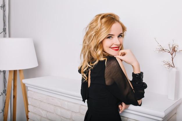 Retrato de primer plano de vista lateral de niña con cabello rubio ondulado en sala blanca moderna con lámpara de pie y chimenea. señora sonriendo, posando. el uso de un elegante vestido negro.