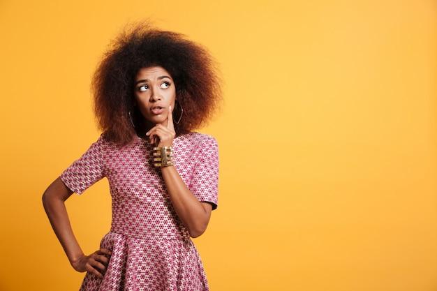 Retrato de primer plano de wooman pensamiento africano con estilo retro tocando su rostro, mirando a un lado