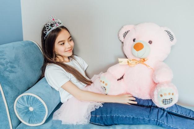 Retrato de princesa feliz jugando con oso rosa y con corona en la cabeza.