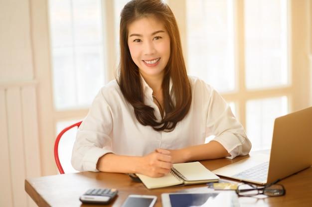 Retrato principal y sonriente de la empresaria asiática sonriente, actitud feliz del éxito. comercio electrónico, tecnología de internet o concepto de pequeña empresa de inicio. oficina moderna o sala de estar con espacio de copia