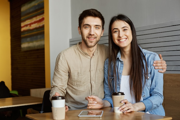 El retrato de los principiantes de la perspectiva alegre se combina con el pelo oscuro en ropa casual, sentado en la cafetería, sonriendo brillante, bebiendo café. y abrazando