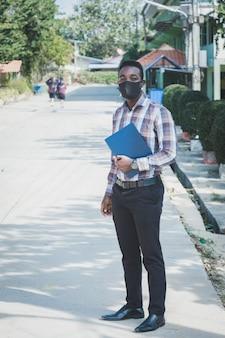 Retrato de profesor africano en mascarilla de pie al aire libre en la escuela