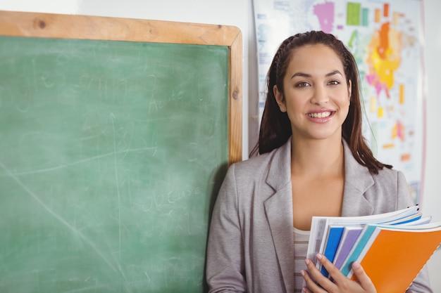Retrato del profesor bonito que sostiene cuadernos en un aula en la escuela