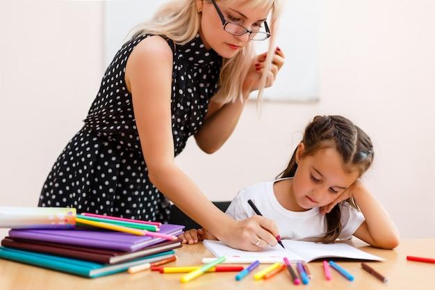 Retrato del profesor mirando a una colegiala de dibujo. cuaderno en la lección
