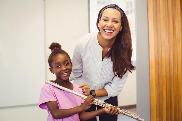 Retrato de profesor y niña con flauta en aula