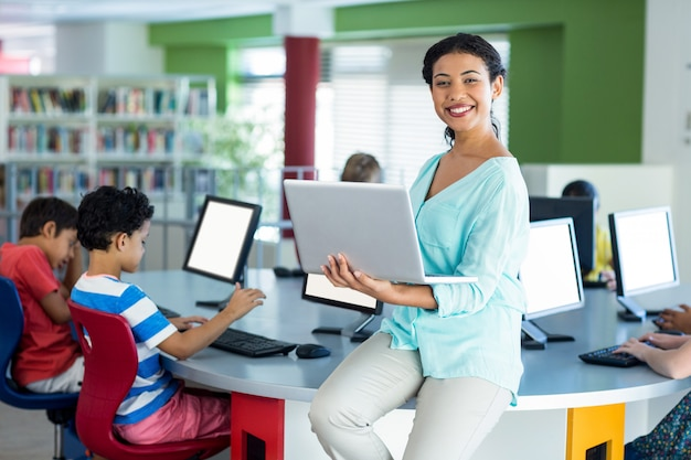 Retrato del profesor sonriente usando laptop
