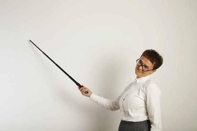 Retrato de una profesora cansada y disgustada con puntero negro y ropa conservadora enseñando una lección en una pizarra en blanco