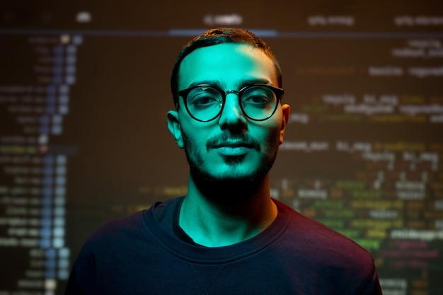 Retrato de programador árabe joven serio en anteojos de pie contra el fondo de codificación