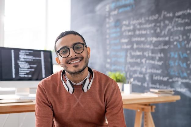 Retrato del programador árabe joven sonriente en anteojos sentado en la oficina moderna de la empresa de ti