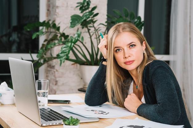 Retrato de un psicólogo femenino joven rubio con el papel de prueba de la mancha de tinta del rorschach y el ordenador portátil