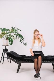 Retrato del psicólogo de sexo femenino que se sienta en el sofá que sostiene el tablero disponible que mira a través de las lentes