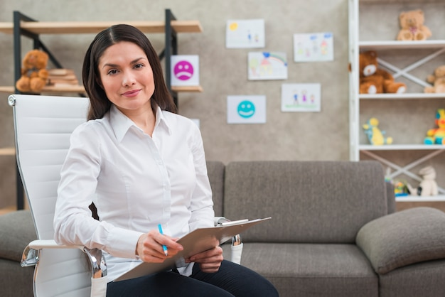 Retrato del psicólogo de sexo femenino sonriente que se sienta en la silla blanca con el tablero y el lápiz en su oficina