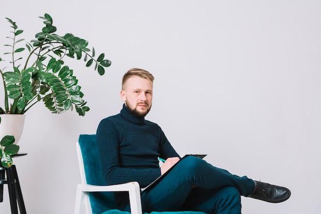 Retrato de un psicólogo de sexo masculino que se sienta en silla con el tablero y la pluma contra la pared blanca