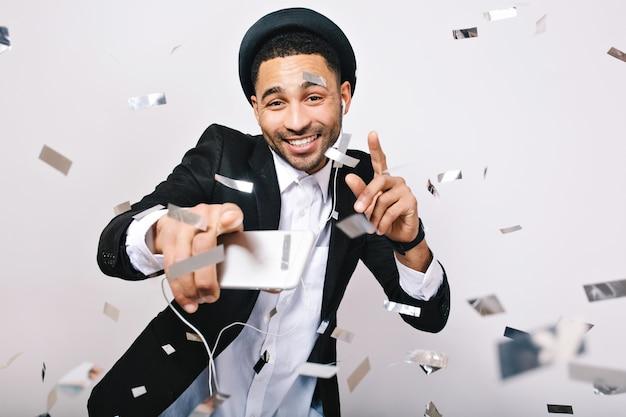 Retrato que expresa emociones verdaderas felices de chico guapo con sombrero, traje divirtiéndose en oropel. celebrando gran fiesta, baile, ocio, fines de semana, buen humor.
