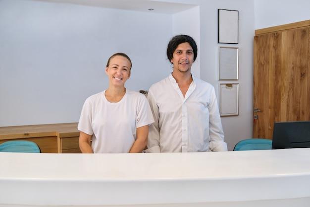 Retrato de recepcionistas de hombre y mujer cerca de recepción