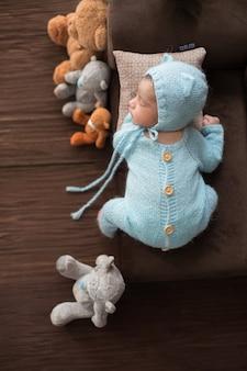 Retrato recién nacido para dormir del pequeño bebé en pijamas azules de ganchillo tendido en un pequeño sofá marrón