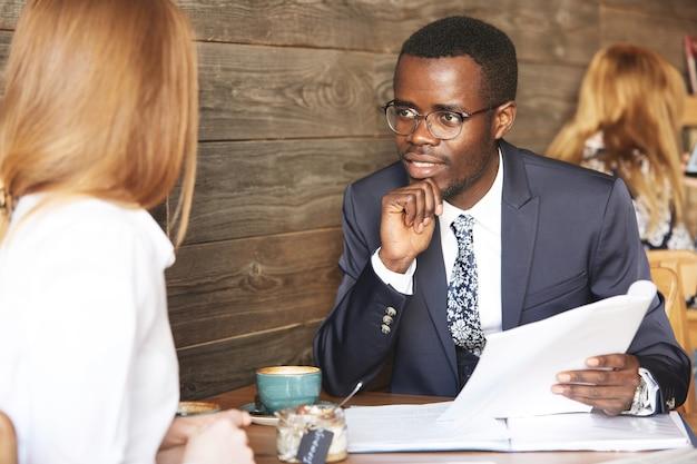 Retrato de reclutador afroamericano en ropa formal entrevistando a solicitante mujer pelirroja