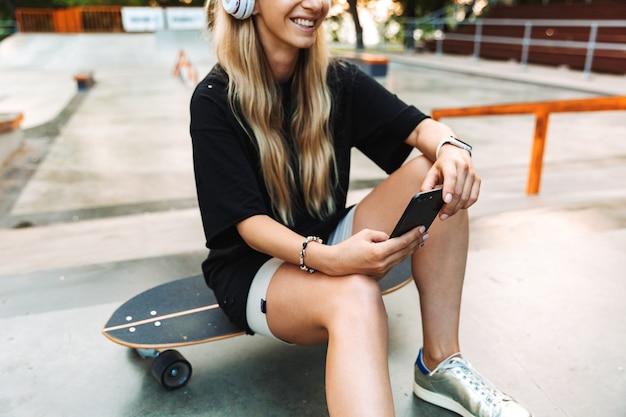 Retrato recortado de una adolescente bastante joven sentada en el skatepark con un longboard, sosteniendo el teléfono móvil mientras escucha música con auriculares