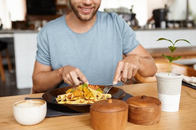 Retrato recortado de feliz joven barbudo en camiseta sonriendo alegremente mientras disfruta de una sabrosa comida durante el almuerzo en el acogedor restaurante, sentado en la mesa de madera