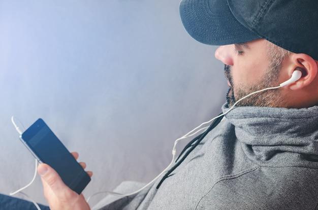 Retrato recortado de hombre barbudo con gorra negra viendo videos o escuchando música con auriculares en el teléfono inteligente. copia espacio