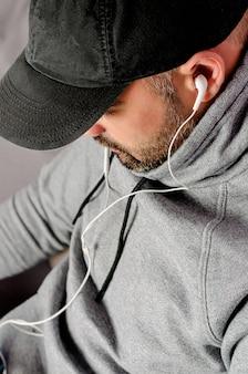 Retrato recortado de hombre barbudo con gorra negra viendo videos o escuchando música con auriculares.