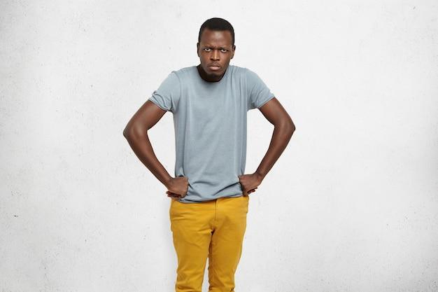 Retrato recortado de un loco hombre afroamericano con camiseta gris y jeans mostaza tomados de la mano en la cadera, frunciendo el ceño, con una mirada gruñona y enojada, insatisfecho con el mal comportamiento de sus pequeños hijos