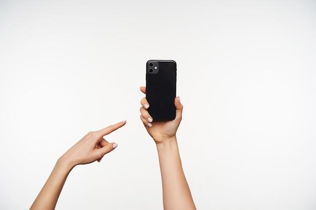 Retrato recortado de las manos de una mujer joven y bien acondicionada manteniendo el teléfono móvil y apuntando con el dedo índice, aislado en blanco