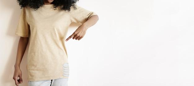 Retrato recortado de modelo de mujer africana joven con ropa casual mostrando su camiseta vacía con el dedo índice
