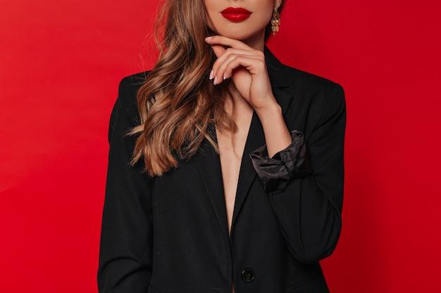 Retrato recortado de una mujer bonita con labios rojos con chaqueta negra posando sobre pared roja