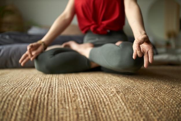 Retrato recortado de mujer descalza en mallas sentada sobre una alfombra en postura de loto practicando meditación para reducir el estrés