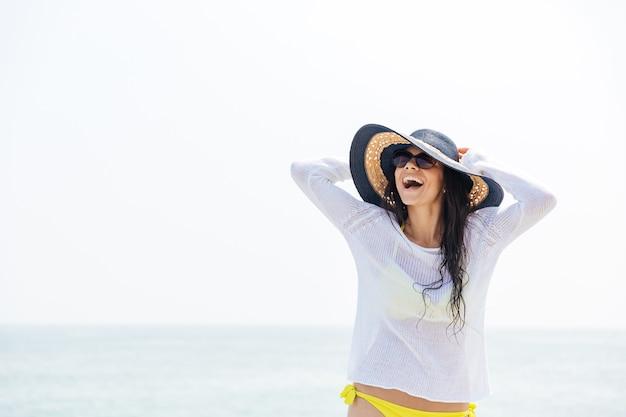 Retrato, de, un, reír, mujer joven, llevando, sombrero de playa, y, biquini, aire libre