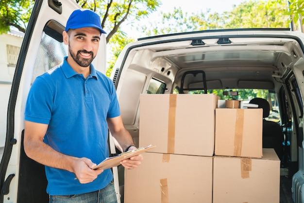 Retrato de un repartidor comprobando los productos en la lista mientras está de pie junto a su camioneta. concepto de entrega y envío.