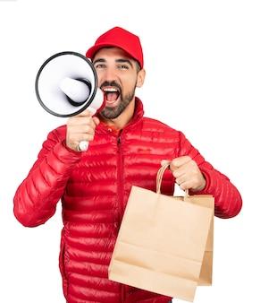 Retrato de un repartidor en ropa de trabajo roja y gritando en megáfono contra el fondo blanco.