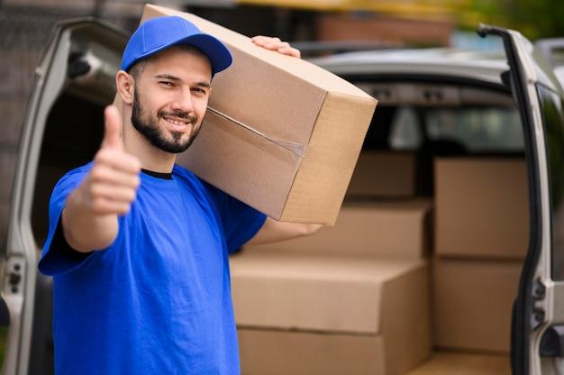 Retrato de repartidor sonriente mostrando el pulgar hacia arriba