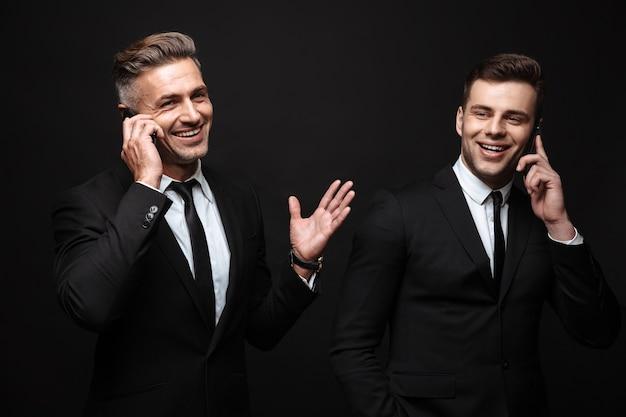 Retrato de la risa de dos hombres de negocios vestidos con traje formal posando en la cámara y hablando por teléfonos móviles aislados sobre pared negra