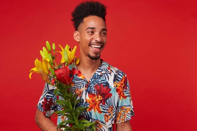 Retrato de risa joven afroamericano, viste camisa hawaiana, mira a la cámara con expresión feliz, sostiene flores amarillas y rojas, se encuentra sobre fondo rojo.
