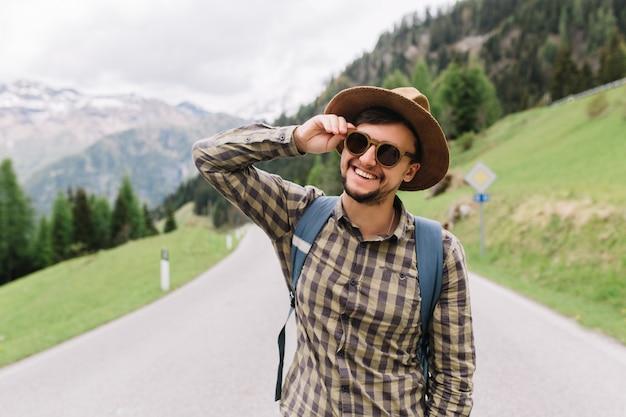 Retrato de risa joven con barba sosteniendo gafas de sol y posando en la carretera en los alpes