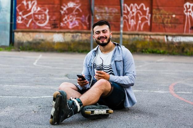 Retrato de un rollerskater masculino joven con teléfono celular y taza de disposición